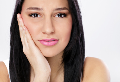 Woman holding side of jaw in pain